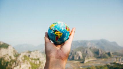 Hand holding miniature globe